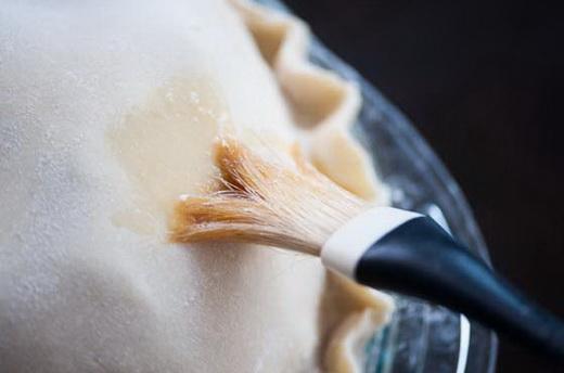 Смазываем верх пирога с малиновым вареньем